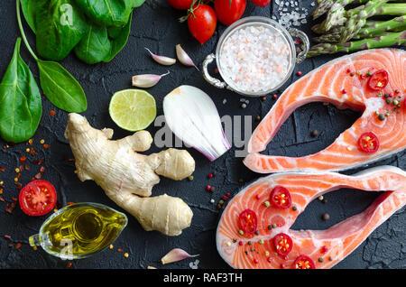 Zwei frischen, rohen Lachs Steaks mit Spargel, Spinat, Knoblauch, Tomaten, Ingwer, Pfefferkörner, Salz, Chili, Zwiebel, Zitrone und Olivenöl auf Schwarz backgrou - Stockfoto