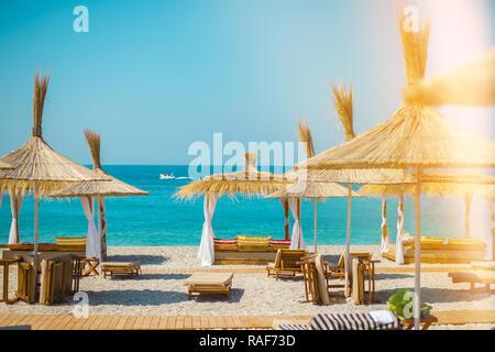 Sonnenschirm Sonnenschirme und Liegestühle am Strand in der Provinz Himare, Albanien. - Stockfoto