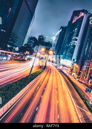 Straßenverkehr in Hongkong bei Nacht. Büro hochhaus Gebäude und viel Verkehr auf Autobahn Straße mit unscharfen Autos leichte Wanderwege. Hongkong, China - Stockfoto