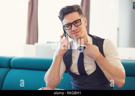 Mann in Gläser, ängstlich, während Sie telefonieren und stirnrunzelnd auf der Couch in der modernen Apartment - Stockfoto