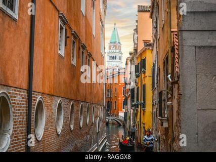 Zwei Gondolieri tragen Touristen auf Gondeln in einem schmalen Kanal mit dem Glockenturm in Aussicht in Venedig, Italien.