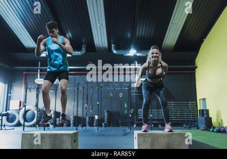 Paar training Springen auf den Feldern im Fitnessstudio, reife Frau und ein junger Mann - Stockfoto