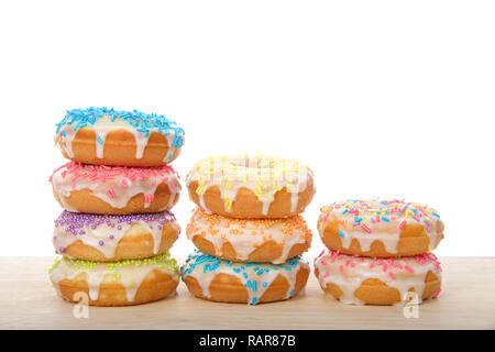 Vielen bunten Milchglas cake Donuts mit Süßigkeiten besprüht in Zeilen Festlegung auf Holz Tabelle auf weißem Hintergrund gestapelt. Spaß festliche Party Food. - Stockfoto