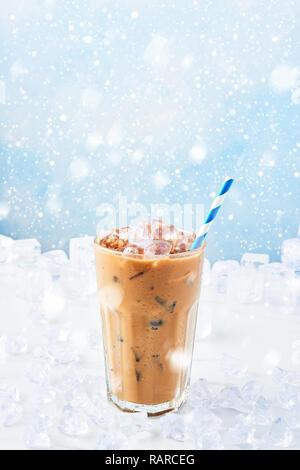 Winter trinken Eis Kaffee mit Sahne in einem hohen Glas mit Stroh durch Eis auf weißem Marmor Tabelle über blauen Hintergrund mit Schnee umgeben. Selektiver Fokus, - Stockfoto