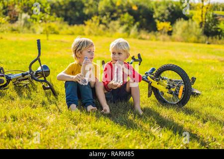 Zwei kleine Jungen Wasser trinken im Park nach dem Reiten ein Fahrrad - Stockfoto
