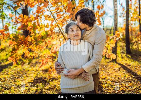 Großmutter und Enkel umarmen im Herbst Park - Stockfoto