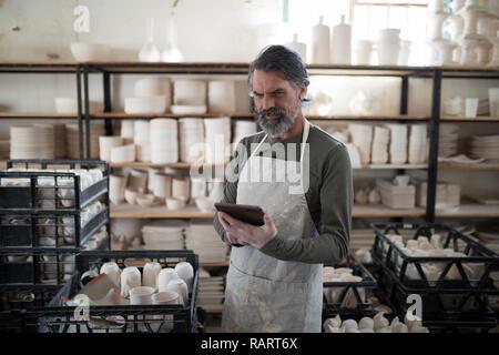 Konzentrierte sich Potter mit Tablet von Arbeit umgeben