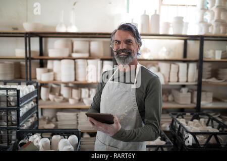 Lächelnd Potter mit Tablet von Arbeit umgeben