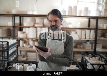 Ernsthafte Potter mit Tablet von Arbeit umgeben