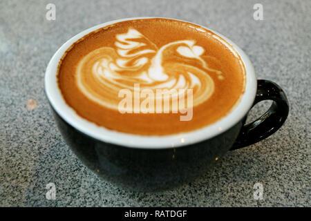 Heißen Cappuccino mit schönen Latte Art in einem schwarzen Schale serviert auf grauem Stein Tabelle Stockfoto