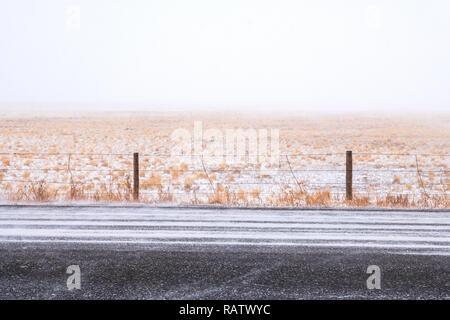 Schnee bedeckt Rt. 285; Ranch Weide & Stacheldraht zaun in der Nähe von Jefferson; Colorado; USA - Stockfoto