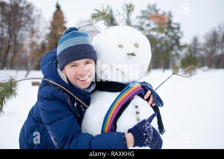 Junge europäische Mann in warme Kleidung, Schneemann aus Schnee outdoor. Spaß wie ein Kind im Winter Urlaub. - Stockfoto