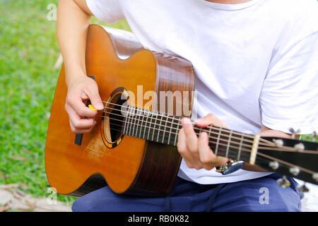 Junge Mann spielt akustische Gitarre im Garten - Stockfoto