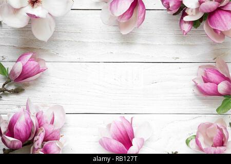 Kreative Gestaltung mit Pink Magnolia Blumen auf weißem Holz- Hintergrund. Flach. top anzeigen. Hochzeit. Feder minimalen Begriff