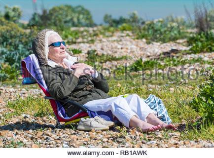 Ältere Frau im Strandkorb sitzen auf einem Strand tragen ein Mantel, an einem windigen und kühlen Frühling im Vereinigten Königreich. - Stockfoto