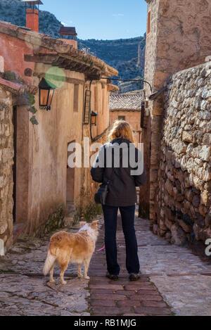Eine blonde Frau, die eine zufällige Kopfsteinpflaster Spanisch Straße in der kleinen Stadt Albarracin mit ihrem blonden Border Collie mix Hund und einem Hauch von Su