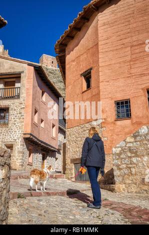 Blonde Frau mit ihrem blonden Border Collie mix Hund auf der kleinen alten verwinkelten Gassen von Albarracin Spanien auf einen hellen klaren Herbst Tag mit einem