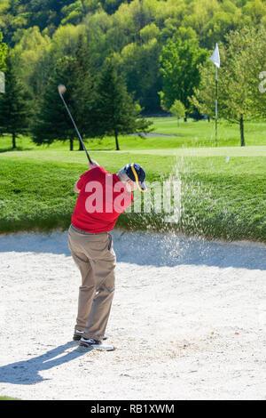 Reife männliche Golfspieler entgeht einem Sandfang, USA - Stockfoto