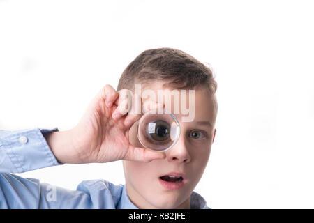 Junge hält ein glas kugel vor seinem Auge und sehen Sie seine Augen vergrößert - Stockfoto