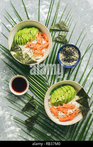 Poke Schüssel mit Lachs Reis und Gemüse auf grauem Hintergrund mit Palmblättern. Traditionelle hawaiische roher Fisch Salat. Ansicht von oben. - Stockfoto