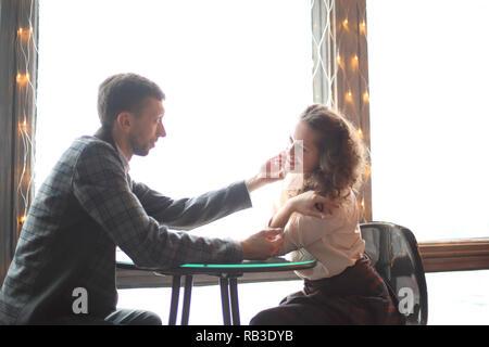 Liebevolle Ehepaar miteinander reden, sitzen in der Nähe der Fenster in ein gemütliches Cafe - Stockfoto