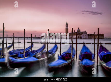 Venedig bei Sonnenaufgang, die Gondeln nach oben und unten bewegen, mit den Wellen im Gegensatz zu der ruhigen Stille des Morgens. - Stockfoto