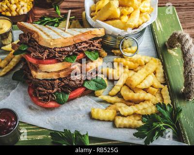 Grill zog beef Sandwich, Toast, Pommes Frites, Sauce, Mais auf einer hölzernen Fach - Stockfoto