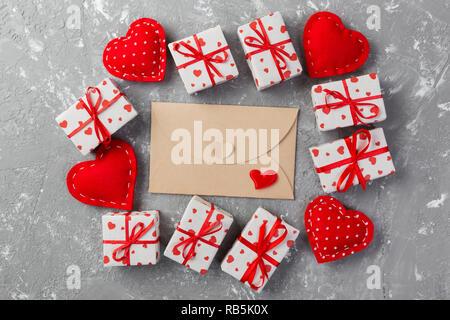 Umschlag Mail mit roten Herzen und Geschenkbox über Grauzement Hintergrund. Valentinstag Karte, Liebe oder Hochzeit Gruß Konzept. - Stockfoto