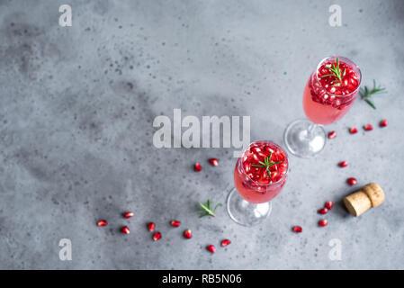 Granatapfel Champagner Mimosa Cocktail (mocktail) mit Rosmarin auf konkreten Hintergrund, kopieren. Mimosa Drink für Valentinstag oder anderen Feiertagen.