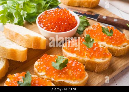 Sandwiches mit roter Lachskaviar auf einem Holzbrett. White Table Top - Stockfoto