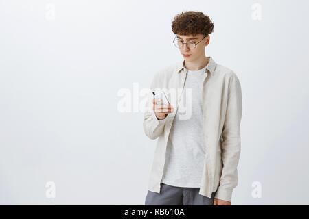 Stilvolle und Kreative junge männliche Freelancer mit Curly Frisur in runde Gläser Kaffee greifen im Cafe scrollen Internet Browser in Smartphones als Warten auf, um das Gerät mit dem Bildschirm nach Ruhe - Stockfoto
