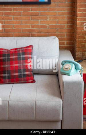Blue vintage Telefon auf ein graues Sofa mit einem roten tartan Kissen, und Mauer. - Stockfoto