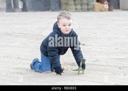 Vier Jahre alten Jungen spielen am Strand und Sand mit seinen Dinosauriern in kühlen Winter Wetter - Stockfoto