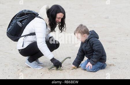 Vier Jahre alten Jungen spielen am Strand und Sand mit seiner Mutter und Dinosaurier in kühlen Winter Wetter - Stockfoto