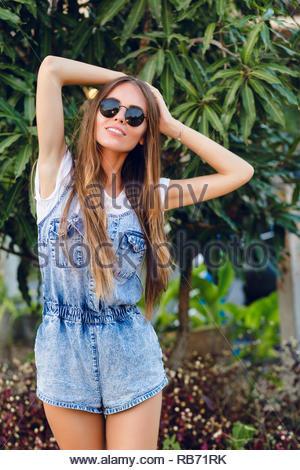 Süße schlanke gebräunte stehendes Mädchen in der Nähe von Tree. Sie trägt weiße t-shirt, denim Shorts und schwarzer Sonnenbrille. Sie hat lange dunkle glatte Haare. Sie lächelt und hält ihre Hände auf den Kopf. - Stockfoto