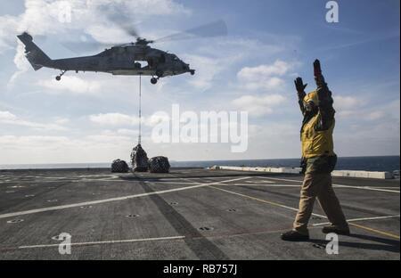 Chief Petty Officer Eugene Williams, eine Landung einweisende mit der Luft Abteilung an Bord der USS Mesa Verde LPD (19), leitet ein MH-60S Seahawk während einer vertikalen Nachschub für den Amphibischen bereit Gruppe Marine Expeditionary Unit Übung Dez. 8, 2016. Während der dreiwöchigen Ausbildung evolution, Marines wird eine breite Palette von Maßnahmen und Szenarien die Verbesserung der Interoperabilität und amphibische Kriegsführung Fähigkeiten mit ihren Marine Pendants bekämpfen. Auffüllung auf See ist entscheidend für die bataan Amphibious Ready Gruppe selbst unterstützen, während im Gange. - Stockfoto