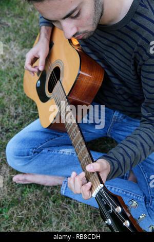 Junge Mann spielt eine Gitarre in einem Garten. Frankreich. - Stockfoto