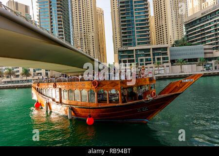 Dubai, VAE 11. 10. 2018: die berühmte traditionelle Holz- alten Dhow Cruise tour in der Marina mit Touristen auf dem Board und moderne Wolkenkratzer in der backgou - Stockfoto