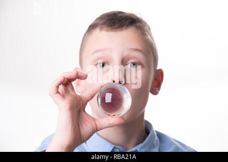 Zukunft - Junge atmet in ein Glas Kugel direkt vor den Mund isoliert auf weißem Hintergrund