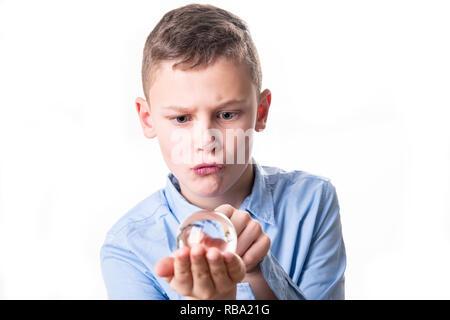 Junge schaut verträumt in eine Glaskugel, um die Zukunft vorauszusagen - Stockfoto