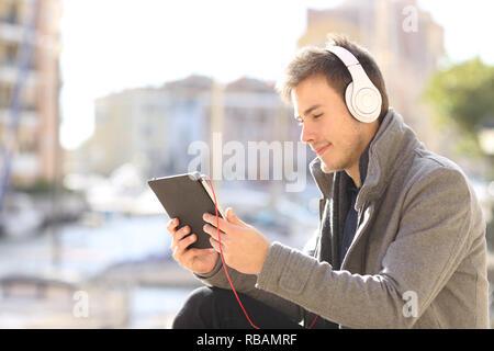 Ernster Mann ansehen und anhören Medien auf eine Tablette in der Straße der Stadt sitzen - Stockfoto