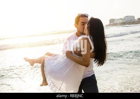 Junge Mann seine Freundin in die Arme am Strand Stockfoto