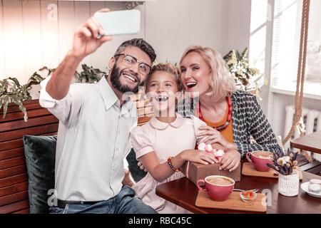 Freudige positive Familie für ein Foto posiert - Stockfoto