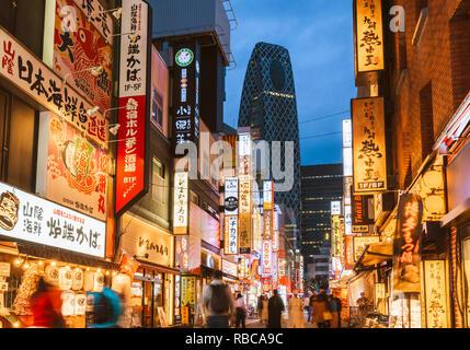 Shinjuku, Tokio, Region Kanto, Japan. Beleuchtete Leuchtreklamen in der Dämmerung und Cocoon Tower im Hintergrund. - Stockfoto