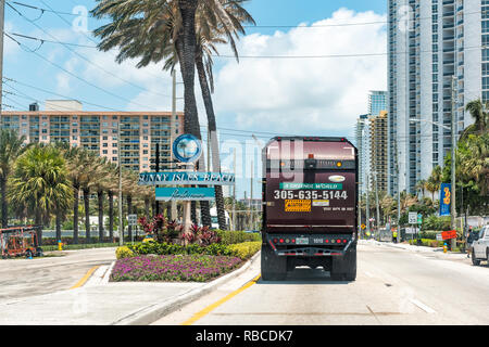 Sunny Isles Beach, USA - Mai 8, 2018: Zeichen für die Stadt im Norden von Miami, Florida, blau Text auf einer 1A der Collins Avenue und der Lkw auf der Straße Straße - Stockfoto
