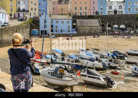 TENBY, Pembrokeshire, Wales - AUGUST 2018: die Person, die ein Foto von dem Hafen von Tenby, West Wales, bei Ebbe. - Stockfoto