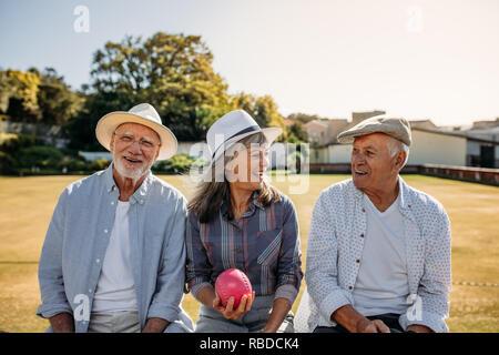 Ältere Frau sitzt mit ihren männlichen Freunde mit einem Boule in der Hand. Alte Freunde, die zusammen sitzen auf einer Bank in einem Park und zu reden. - Stockfoto