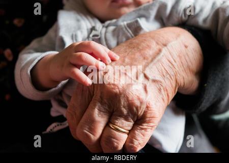 Kleines Baby Hand berühren und streicheln alte Großmutter hand mit Falten, Symbol der Generationen - Stockfoto