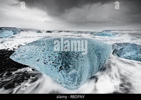 Großer Block aus Eis in Blautönen an einem Strand mit starker Brandung, das Wasser Bewegung gesehen werden kann (lange Belichtung, Spuren der Bewegung), vor einem kontrastierenden werden - Stockfoto