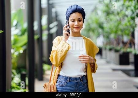 Eine junge und schöne Orientalische Frau in einem turban Hijab ist Lächeln, wie Sie auf Ihrem Smartphone die Gespräche auf der Straße während des Tages. - Stockfoto